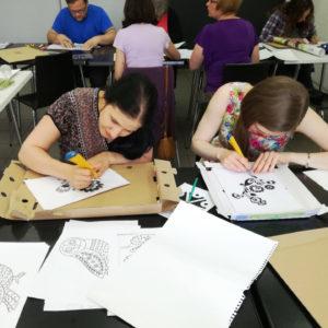 Zdjęcie przedstawia kilka osób wykonujących rysunki z motywami słowiańskimi podczas zajęć z kultury i języka słowiańskiego SLAVICA
