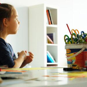 Zdjęcie przedstawia siedzącą przy stoliku dziewczynkę podczas zajęć plastycznych, na stole obok dziewczynki znajdują się przyrządy plastyczne