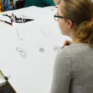 Zdjęcie przedstawia dziewczyną szkicującą podczas zajęć z rysunku