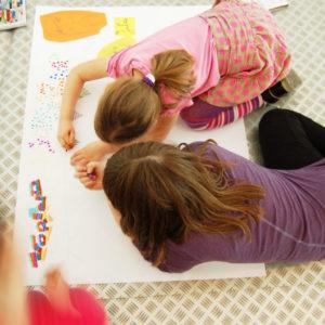 Zdjęcie przedstawia dzieci wykonujący duży kolorowy rysunek podczas zajęć plastycznych