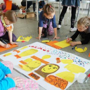 Zdjęcie przedstawia dzieci wykonujące dużą pracę rysunkową wyklejaną kolorowym papierem podczas zajęć plastycznych