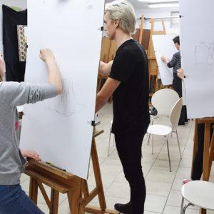 Zdjęcie przedstawia kilka osób szkicujących przy sztalugach podczas zajęć z rysunku