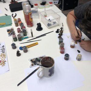 """Zdjęcie przedstawia osobę malującą figurkę w ramach spotkania """"Zagraj w TCK"""""""