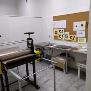 Zdjęcie przedstawia prasę graficzną oraz wiszące na tablicy korkowej odbitki prac graficznych uczniów zajęć