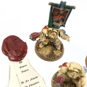 Zdjęcie przedstawia figurki praz pieczęć z planszowej gry strategicznej w stylu fantasy
