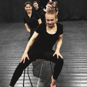 """Zdjęcie przedstawia grupę teatralną """"Teraz ja"""" a czarnych ubranich na scenie sali widowiskowej TCK"""