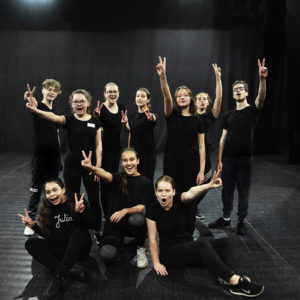 """Zdjęcie przedstawia grupę teatralną """"Tarnogórski Teatr Młodych"""" w czarnych ubranich na scenie sali widowiskowej TCK"""