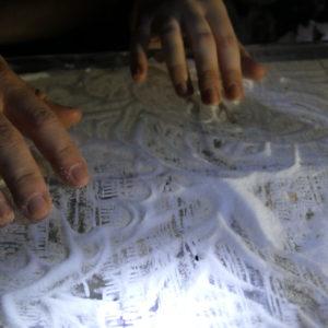 Zdjęcie przedstawia dłonie oraz sól rozsypaną na podłodze Galerii Przytyk w ramach instalacji artystycznej