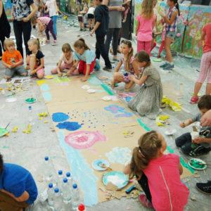 Zdjęcie przedstawia dzieci i rodziców tworzących duże prace plastyczne na podłodze holu tCK