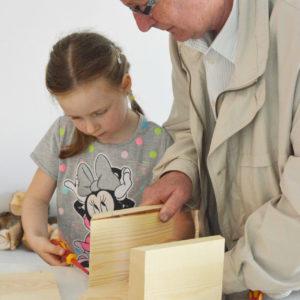 Zdjęcie przedstawia dziewczynę wraz z dziadkiem podczas warsztatów tworzenia budek lęgowych dla ptaków