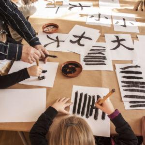 Zdjecie przedstawia uczestników zajęć z kultury Japonii podczas nauki kaligrafii