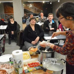 Zdjęcie przedstawia prowadzącą oraz uczestników na zajęciach kulinarnych w ramach spotkań z kulturą Japonii