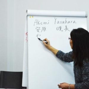 Zdjęcie przedstawia Japonkę piszącą swoje nazwisko na białej tablicy