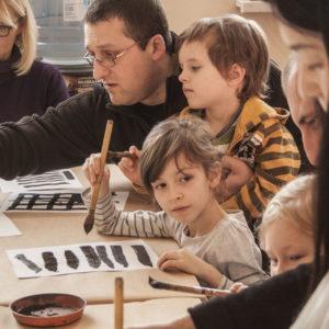Zdjęcie przedstawia uczestników zajęć z kultury Japonii uczących się kaligrafii