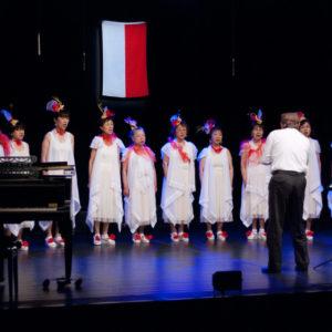 Zdjęcie przedstawia chórzystki japońskie podczas konceru