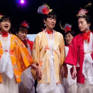 Zdjęcie przedstawia chórzystki w tradycyjnych strojach japońskich podczas koncertu