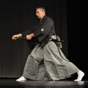 Zdjęcie przedstawia mężczyznę ubranego w tradycyjny strój japońskich samurajów