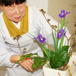 Zdjęcie przedstawia Japonkę oraz bukiet kwiatów wykonany w ramach zasad sztuki ikebana