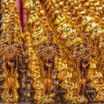 Zdjęcie przedstawia ustawione w rzędach figury Oskarów filmowych