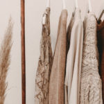 Zdjęcie przedstawia wiszące na wieszakach swetry w odcieniach beżów i brązów