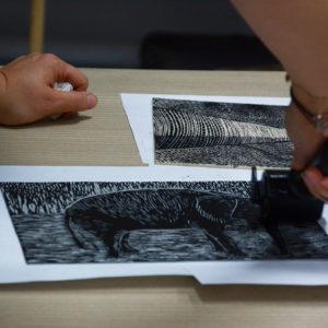 Zdjęcie przedstawia proces powstawania odbitek linorytu podczas warsztatów graficznych