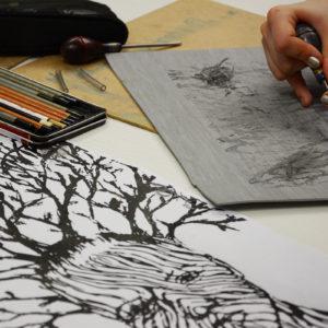 Zdjęcie przedstawia proces powstawania linorytu podczas warsztatów graficznych