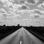 Zdjęcie przedstawia zwężającą się ku górze asfaltową ulicę