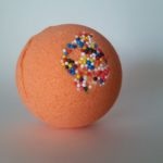 Zdjęcie przedstawia pomarańczową kulę do kąpieli, ozdobioną małymi, kolorowymi kuleczkami