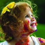 Zdjęcie przedstawia uśmiechniętą twarz dziecka z twarzą pomalowaną kolorowymi farbami