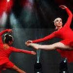 Zdjęcie przedstawia dwie tancerki w czerwonych sukniach