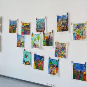 """Zdjęcie przedstawia wiszące na ścianie prace z wystawy uczestników zajęć plastycznych """"Punkt Sztuki"""""""