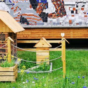 Zdjęcie przedstawia hotelik dla owadów i domek dla jeża znajdujące się na trawniku przed TCK