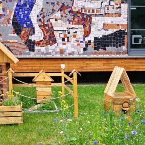 Zdjęcie przedstawia hotelik dla owadów, domek dla kotów i dla jeża znajdujące się na trawniku przed TCK