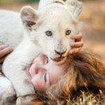 """Kadr z filmu """"Mia i biały lew"""" przedstawia dziewczynkę leżącą na trawię z młodym, bialym lwiątkiem"""
