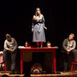 """Kadr ze spektaklu """"Jo był ukradziony"""" przedstawia stojącą na stole kobietę, mężczyznę schowanego pod stołem, dwie kobiety klękające z tyłu oraz dwóch mężczyzn po obu stronach stołu"""