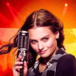 """Fragment plakat filmu """"Jak zostać gwiazdą"""" przedstawiającego młodą piosenkarkę przy mikrofonie"""
