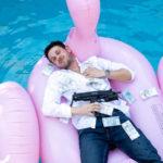 """Kadr z filmu """"Pętla"""" przedstawiajacy obsypanego pieniędzmi mężczyznę z bronią pływającego w basenie na różowym flamingu"""