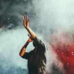 Zdjęcie przedstawia śpiewajacego do mikrofonu mężczyznę z wyciągniętą ku górze dłonią pokazującą cztery palce