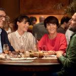 """Kadr z filmu """"Małe szczęścia"""" przedstawiający grupkę roześmianych osób przy stole restauracji"""