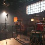 Zdjęcie przedstawia studio nagraniowe z perkusją i mikrofonem i pianinem