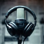 Zdjęcie przedstawia słuchawki przewieszone przez mikrofon do wokalu