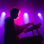 Zdjęcie przedstawia mężczyznę grającego na keyboardzie elektronicznym