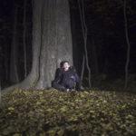 Zdjęcie wykonane nocą przedstawia siedzącego pod drzewem, krzyczącego chłopaka.