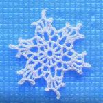 zdjęcie białej szydełkowej śnieżynki na niebieskim tle