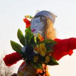 Zdjęcie przedstawia kolorową, ręcznie zrobioną marzannę z kolorowych tkanin i ozdobioną kwiatami.