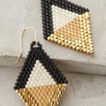 Zdjęcie przedstawia parę geometrycznych kolczyków wykonanych z koralików w kolorach złota, beżu i czerni.