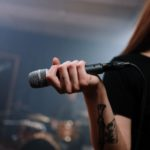 na zdjęciu wytatuowana ręka trzymająca mikrofon