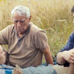 """zdjęcie z filmu """"Każdy ma swoje lato"""" przedstawiające starszego mężczyznę, jego syna oraz leżąca kobietę, sytuacja dzieje się na łące"""