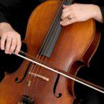 zdjęcie wiolonczeli i rąk trzymających smyczek i grających na nim
