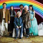 """Zdjęcie przedstawia azjatycką rodzinę ubraną w eleganckie stroje na tle sztucznej tęczy. Kadr z filmu """"Kłamstewka"""""""